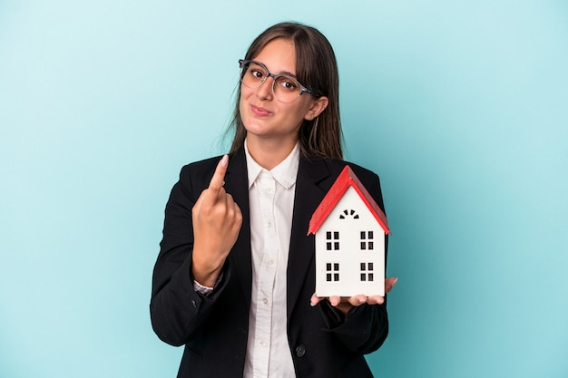 Young business woman holding a toy home isolated on blue background pointing with finger at you as if inviting come closer.