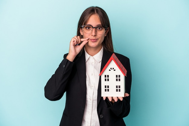 Young business woman holding a toy home isolated on blue background with fingers on lips keeping a secret.