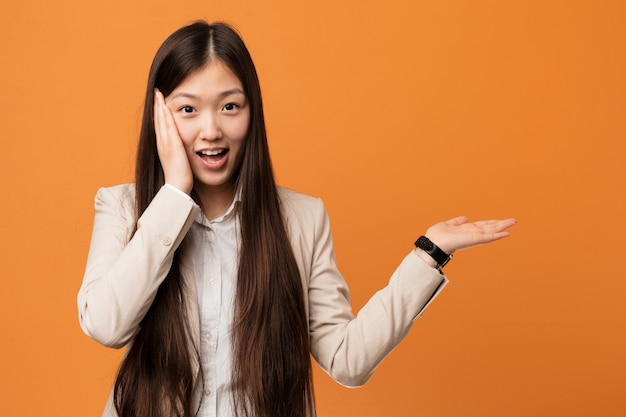Young business woman holds something on a palm