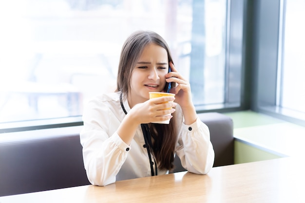 카페에서 스마트폰으로 이야기하고 웃고 커피를 마시는 젊은 비즈니스 우먼
