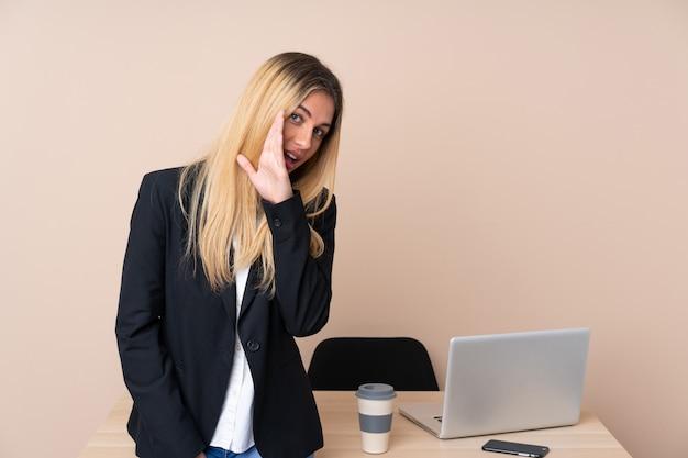 何かをささやくオフィスで若いビジネス女性
