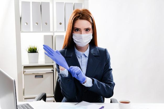 Молодой бизнес женщина в защитной маске работает на компьютере в офисе. девушка одевает резиновые перчатки