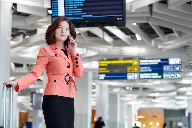 Молодая деловая женщина в аэропорту с багажом, разговаривает по телефону и улыбается.