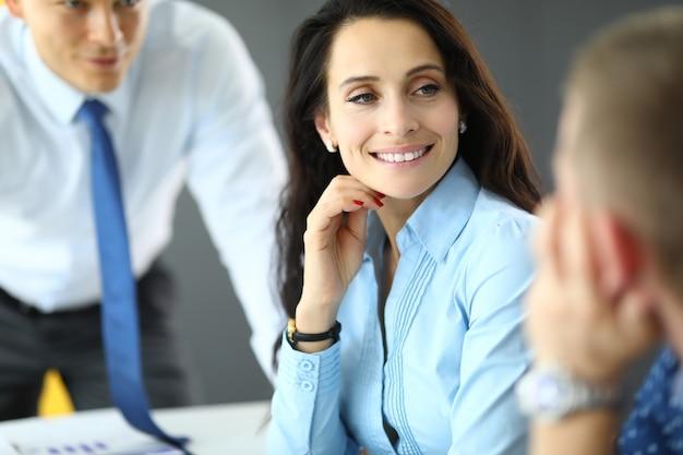 青いシャツの若いビジネス女性は、オフィスの肖像画で2人の男性と通信します