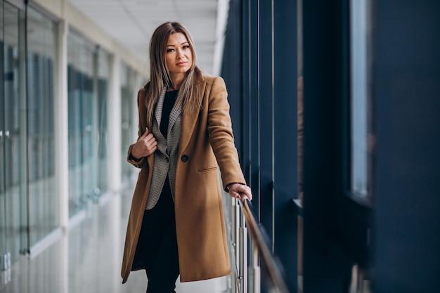 ターミナルで待っているコートの若いビジネス女性