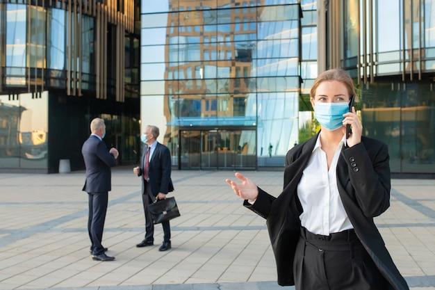 屋外で携帯電話で話しているフェイスマスクとオフィススーツの若いビジネス女性。バックグラウンドでのビジネスマンや都市の建物。スペースをコピーします。ビジネスと流行のコンセプト