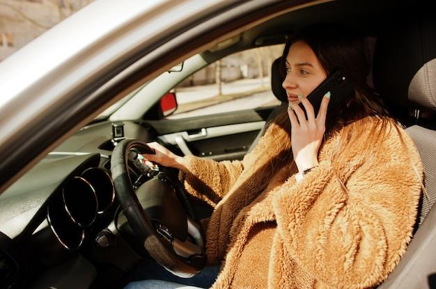 車のホイールに座って携帯電話で話す毛皮の若いビジネス女性。