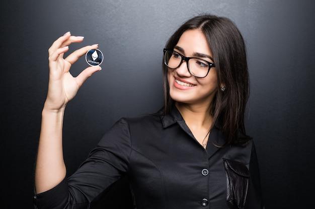 Молодая деловая женщина в очках с litecoin в руках, изолированных на черной стене.