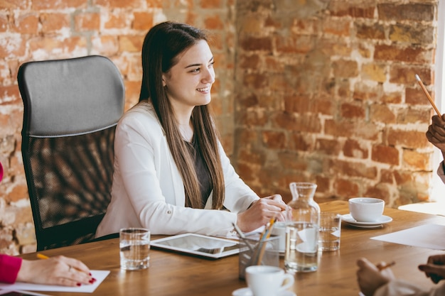 Молодая деловая женщина в современном офисе с командой. творческая встреча, обсуждение, работа над проектом. понятие финансов, бизнеса, женской силы, включения, разнообразия, феминизма. выглядит счастливым и внимательным.