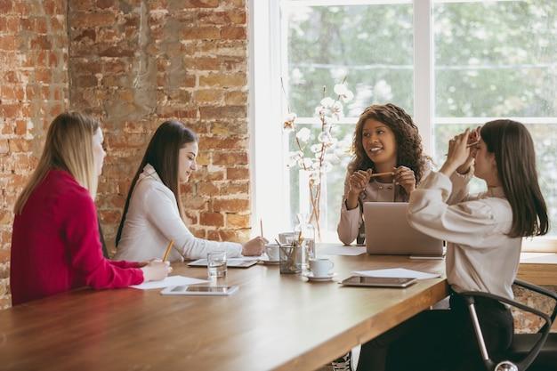 Молодая деловая женщина в современном офисе с командой. творческая встреча, постановка задач. закройте графики аналитики. понятие финансов, бизнеса, женской силы, включения, разнообразия, феминизма. обсуждение.