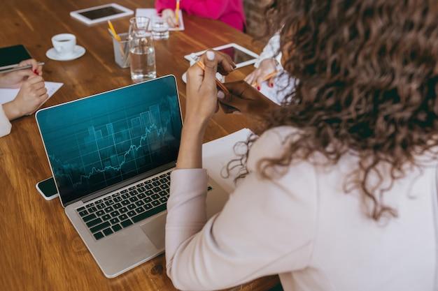 Молодая деловая женщина в современном офисе с командой. творческая встреча, постановка задач. закройте графики аналитики. понятие финансов, бизнеса, женской силы, включения, разнообразия, феминизма. вид сверху.