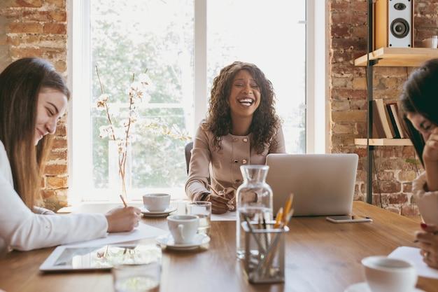 Молодая деловая женщина в современном офисе с командой. творческая встреча, постановка задач. улыбка, восторг, совместная работа. обсуждение концепции финансов, бизнеса, женской силы, инклюзивности, разнообразия, феминизма