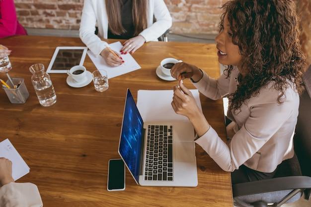 Молодая деловая женщина в современном офисе с командой, давая задачи творческой встречи