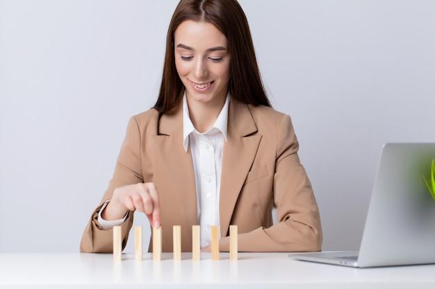 オフィスで若いビジネス女性は木製キューブになります