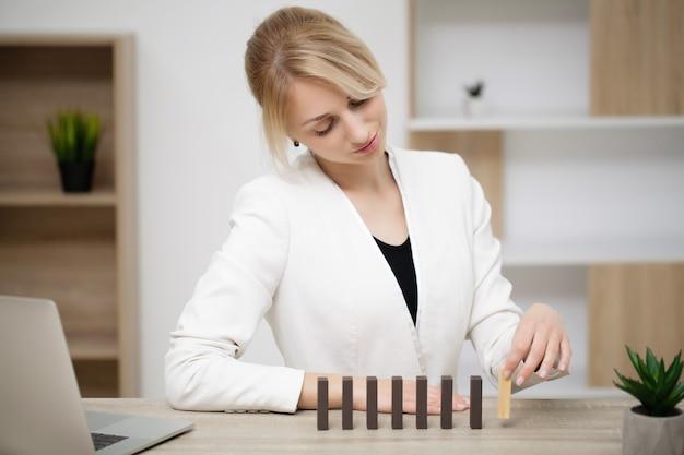 Молодая деловая женщина в офисе делает деревянные кубики.
