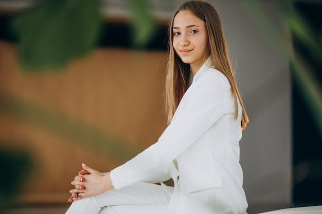 Молодая бизнес-леди в белом костюме на студии