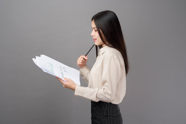 Young business woman is analyzing business plan on gray background