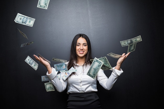 Young business woman is standing in the rain of the dollar bills on black wall