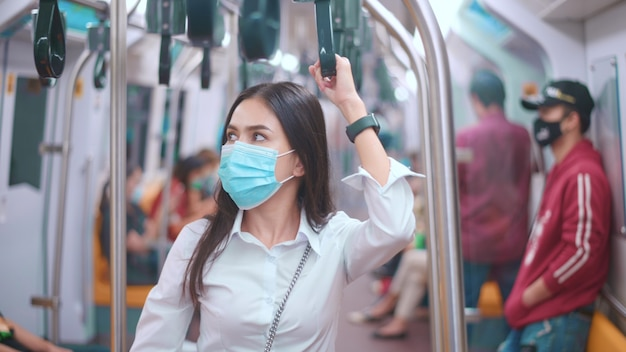 A young business woman is wearing face mask in public transportation , safety travel , covid-19 protection concept.