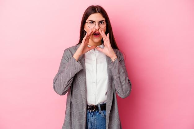 Молодая деловая женщина изолирована на розовой стене и кричит взволнованно