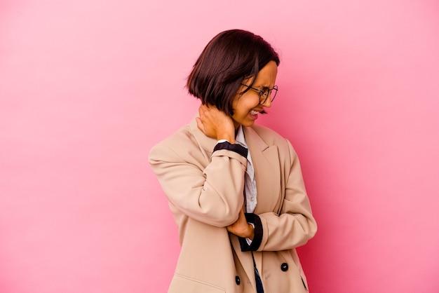 座りがちな生活のために首の痛みに苦しんでピンクの壁に孤立した若いビジネスウーマン