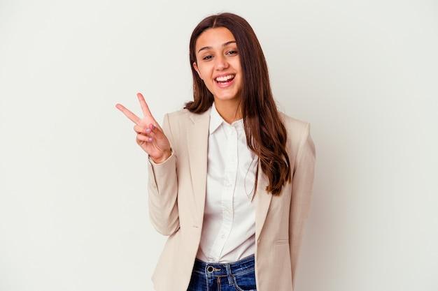 指で平和のシンボルを示す楽しくてのんきな白い壁に孤立した若いビジネス女性