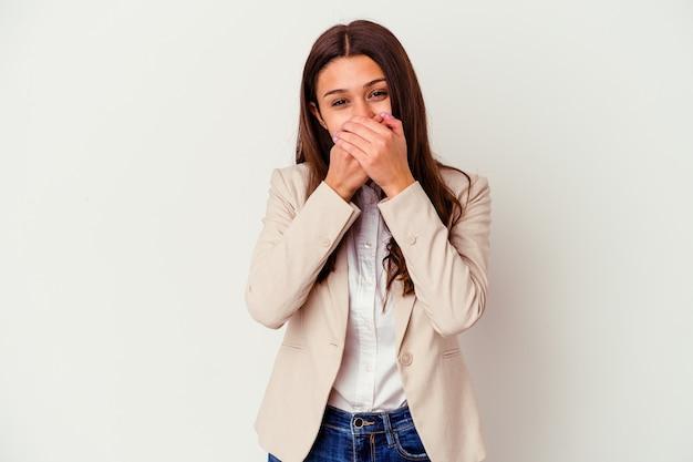白い壁に孤立した若いビジネス女性は手で口を覆ってショック