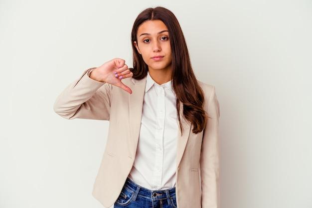 Молодая деловая женщина изолирована на белой стене, показывая жест неприязни, пальцы вниз