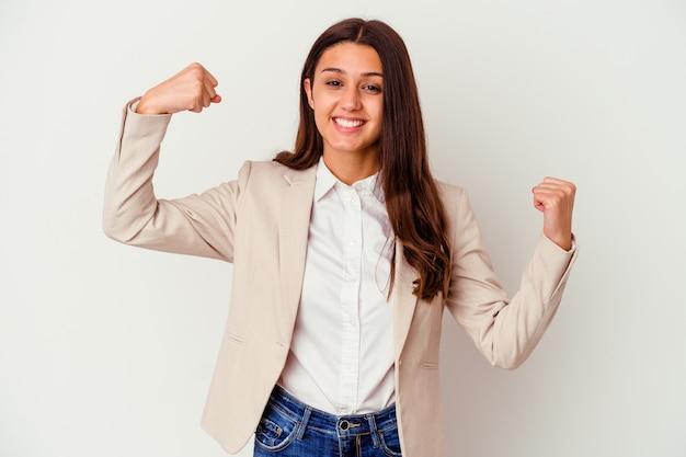 腕で強さのジェスチャーを示す白い壁に分離された若いビジネス女性