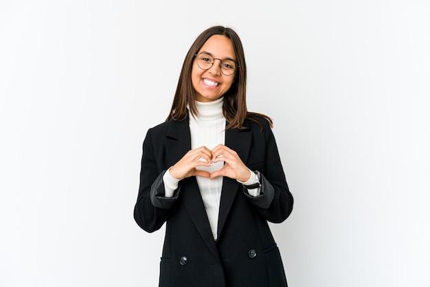 笑顔と手でハートの形を示す白い壁に分離された若いビジネス女性