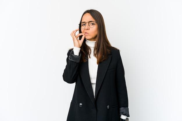 秘密を保持している唇に指で白い壁に分離された若いビジネス女性