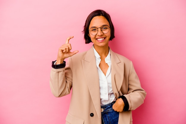Young business woman isolated on pink wall holding something little with forefingers, smiling and confident