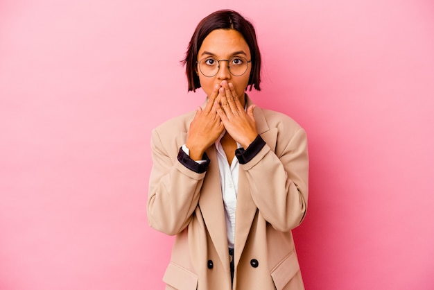 Young business woman isolated on pink wall shocked covering mouth with hands