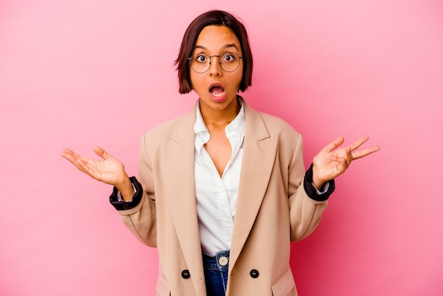 Young business woman isolated on pink wall surprised and shocked
