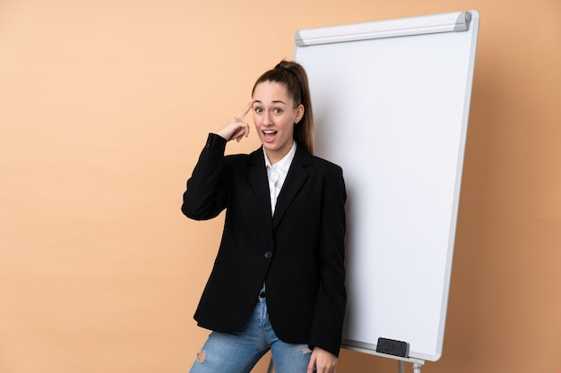 Young business woman over isolated wall giving a presentation on white board and intending to realizes the solution
