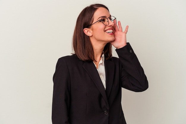 Young business woman isolated on white background shouting and holding palm near opened mouth.