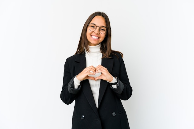 Young business woman isolated on white wall smiling and showing a heart shape with hands