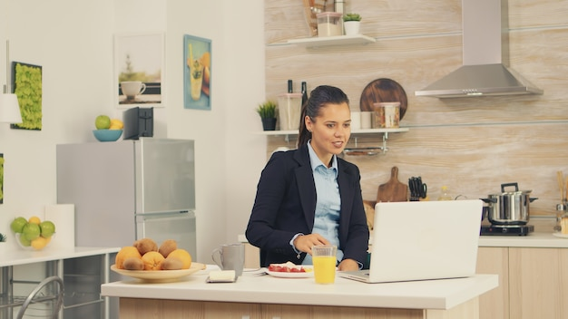 Young business woman in the kitchen having a healthy meal while talking on a video call with her colleagues from the office, using modern technology and working around the clock