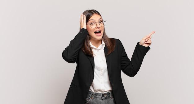 Молодая деловая женщина смеется, выглядит счастливой, позитивной и удивленной, осознавая отличную идею, указывающую на боковую копию пространства