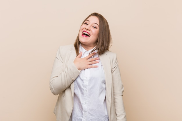 Young business woman laughs out loudly keeping hand on chest.