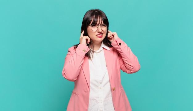 怒り、ストレス、イライラしているように見え、耳をつんざくような音、音、または大音量の音楽で両耳を覆っている若いビジネスウーマン