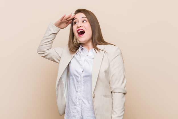 Young business woman looking far away keeping hand on forehead.