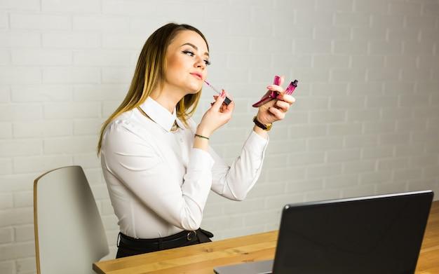 젊은 비즈니스 여자는 거울을보고 그녀의 직장에서 립스틱을 사용