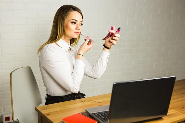 거울을보고 그녀의 worlplace에서 립스틱을 사용 하여 젊은 비즈니스 여자.