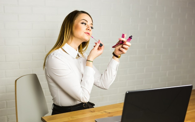 Young business woman looking in the mirror and using lipstick at her workplace