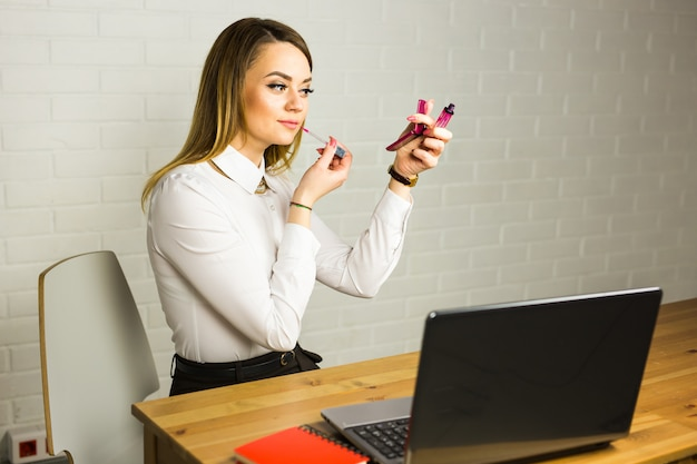 Young business woman looking in the mirror and using lipstick at her worlplace.