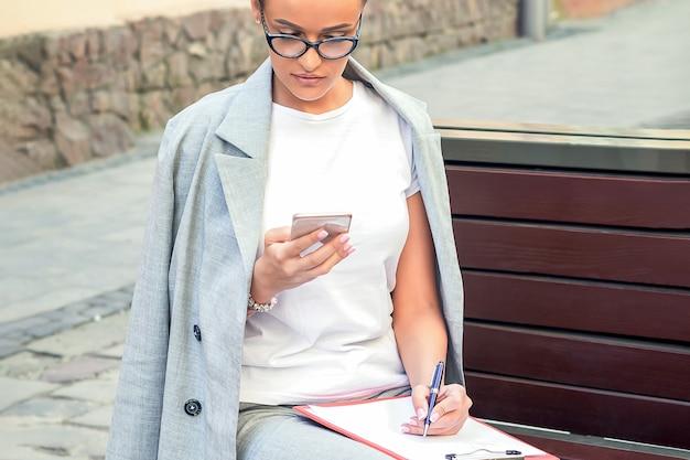 Молодая деловая женщина, глядя на смартфон на скамейке