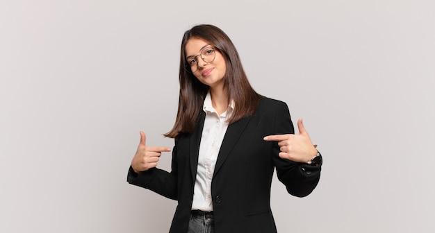 誇らしげに、傲慢で、幸せで、驚き、満足しているように見え、自己を指し、勝者のように感じている若いビジネスウーマン