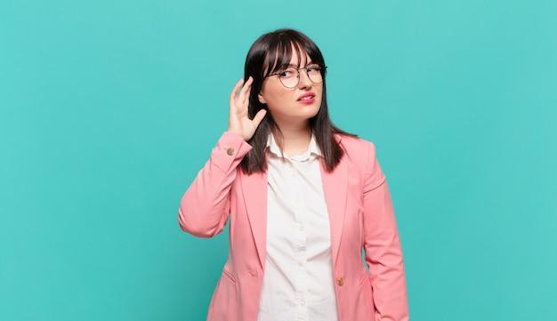 Молодая деловая женщина выглядит серьезной и любопытной, слушает, пытается услышать секретный разговор или сплетню, подслушивает