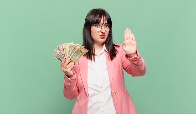 Young business woman looking serious, stern, displeased and angry showing open palm making stop gesture